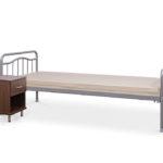 hotelowe łóżko metalowe i szafka przyłóżkowa